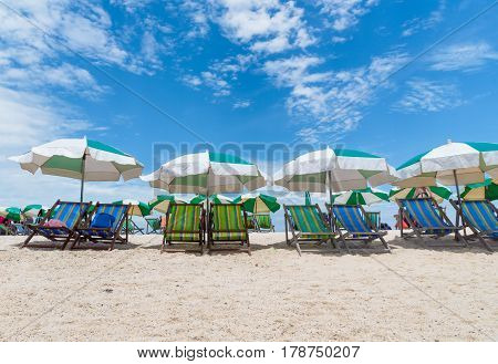 Beach chairs with umbrella with blue sky on tropical beach at Koh Tao Thailand.