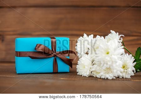 Wooden background with a gift and flowers for congratulations. The concept of Mother's Day birthday March 8.