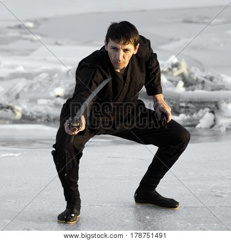 Black ninja with sword is practicing martial arts on the ice at winter.