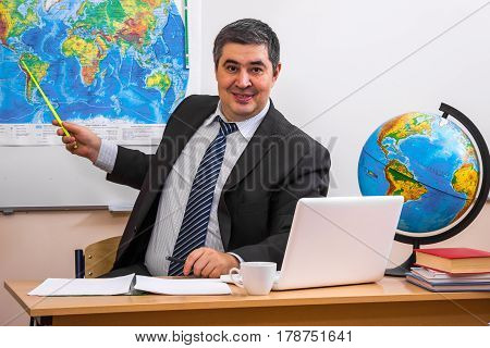 A male teacher leads a lesson in geography. The teacher shows a pointer to the world map. There is a lesson.