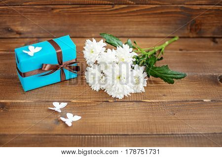 Wooden background with a gift and flowers and butterflies. The concept of Mother's Day birthday March 8.
