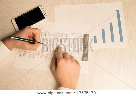 Man In White Shirt Working With Graphs And Charts. In The Frame Just Hands And Paper.