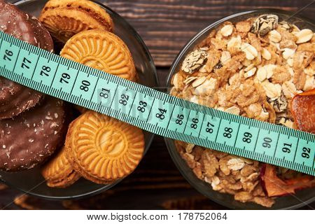 Muesli, cookies and measuring tape. Healthy and unhealthy food.