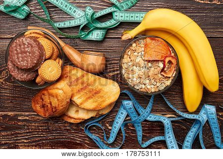 Measuring tapes, fruits and sweets. Struggle to get healthy.