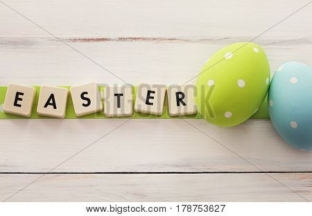 Easter scrabble with 2 polka dots eggs on a wooden background