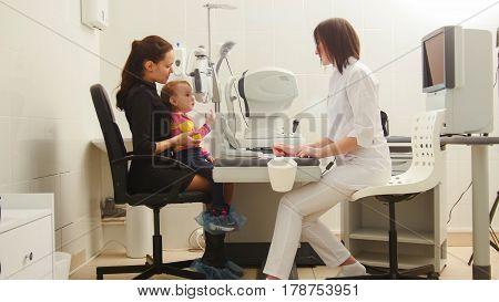 Child with Mother in eye clinic - children ophthalmology - optometrist Checks Child's Eye, horizontal