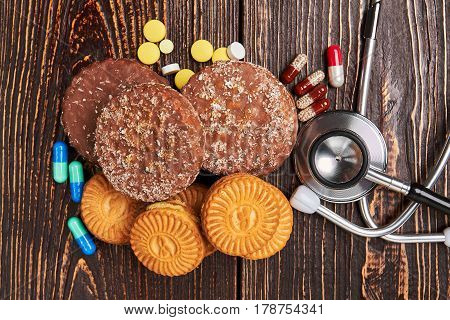 Stethoscope, cookies and medicines. Signs and symptoms of diabetes.
