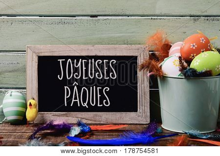 a chalkboard with the text joyeuses paques, happy easter in French, hanging on a rustic wooden wall, and a pile of different decorated easter eggs, a teddy chick and feathers of different colors