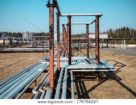 Steel pipes at the oil depot against the background of tanks