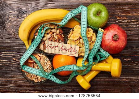 Muesli, orange and sport equipment. Get healthy program.