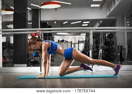 Attractive young woman is doing plank exercise while working out in gym. Beautiful slender brunette girl in blue sportswear.