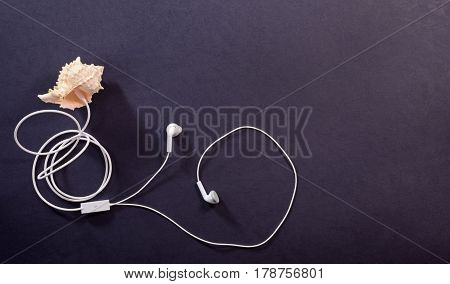 Travel concept. White headphones and seashell on a dark background closeup listen to the sound of the sea