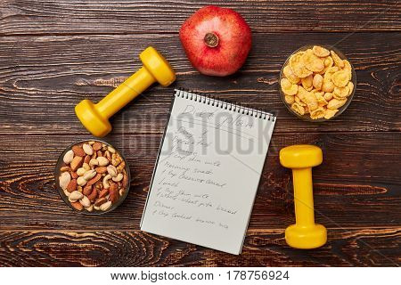 Dumbbells, notebook, cereals and fruit. Exercise and nutrition plan.