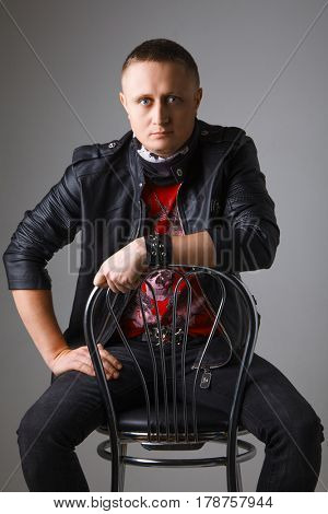 Stylish young brunet in leather jacket sitting on chair