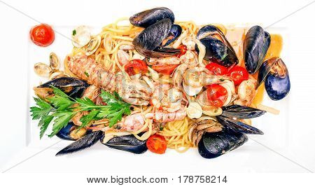 Seafood spaghetti fish sauce top view image on white porcelain rectangular dish