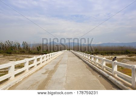 a white stone bridge over the river sutlej in the countryside of the punjab north india under a blue cloudy sky