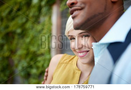 Pretty short hair blond girlfriend and handsome African American boyfriend on a date, enjoying a romantic moment together outside