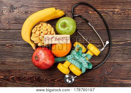 Stethoscope, fruits and sport equipment. A healthy way of life.