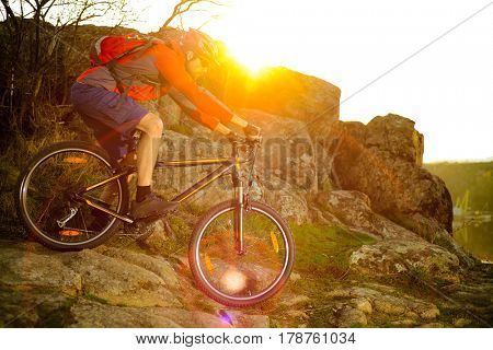 Cyclist Riding the Mountain Bike Down Rocky Hill on the Spring Trail at Sunset. Extreme Sports Concept.