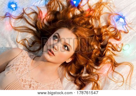Portrait of pretty redhead woman. Beautiful girl lying on the bed.