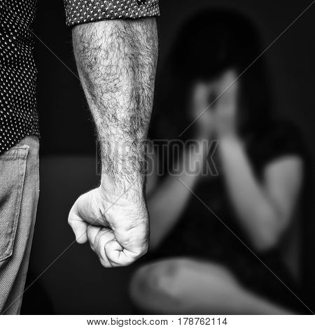 Domestic or gender violence - Aggressive man with a clenched fist threatens to hit a scared woman