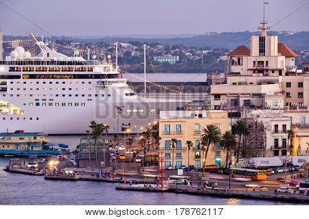Old Havana at sunset with a view of historic buildings and a modern cruise ship docked at the bay
