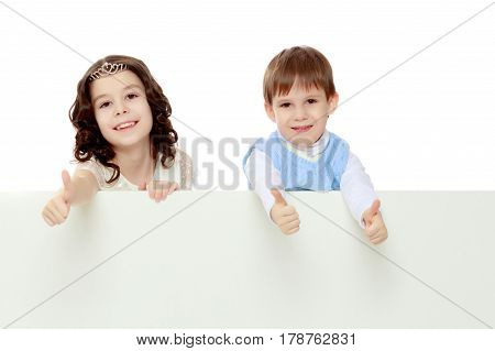 A boy and a girl peeping from behind the white banner.Children show a gesture all okay.