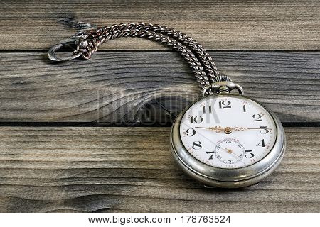 Image of an elegant antique pocket watch photographed on an old wooden table