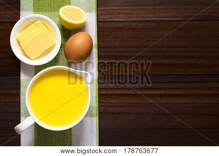 Hollandaise sauce a basic sauce of the French cuisine served in a sauce boat with ingredients (egg butter lemon) on the side photographed overhead on dark wood with natural light