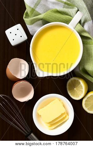 Hollandaise sauce a basic sauce of the French cuisine served in a sauce boat with ingredients (egg butter lemon) and whisk on the side photographed overhead on dark wood with natural light