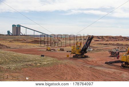 Industrial coal mining equipment and silos beside a row of railway cars in a Wyoming valley landscape