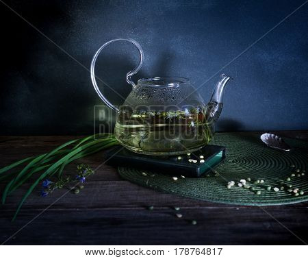 Boiling water and grass in a glass teapot. Dark background. Vintage