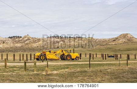 A yellow dirt scraper parked by a pasture fence in a valley surrounded by rocky hills in a Wyoming landscape