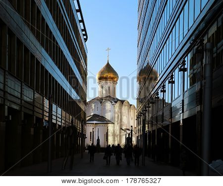 Beautiful Church with Golden dome is photographed in close-up between tall buildings