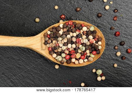ladle with a mix of peppercorns on black stone