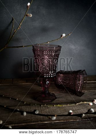 Two vintage glasses on a wooden table, willow branches. Dark background.
