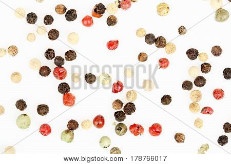 three types of peppercorns on white surface
