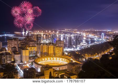 Aerial view of illuminated city in night and firework above it.