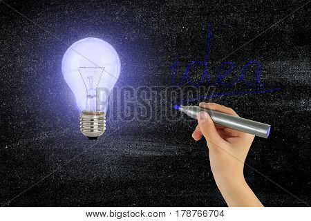 light bulb and hand writing idea on black board idea concept