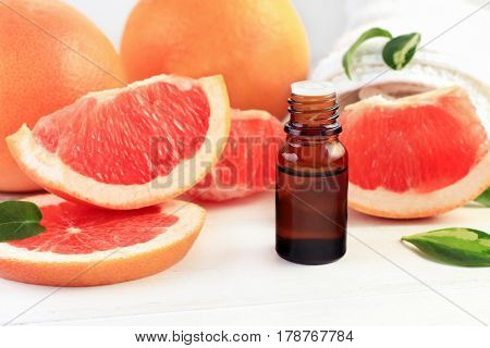Grapefruit fragrance oil in apothecary dark glass dropper bottle of liquid cosmetic product, fresh pink citrus fruit pulp in pieces. Sweet natural aromatherapy spa and health care.