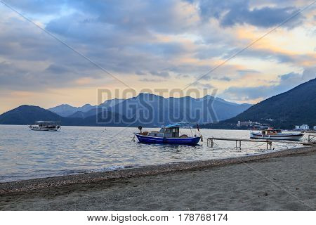 Marmaris beach with fishing boats on mountains background