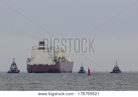TANKER AND TUGS - Tugboats assists on a big ship sailing on a cruise