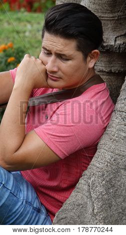 Sad Confused Man Leaning Against a Tree