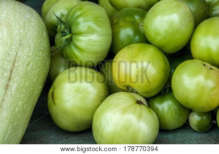 A bunch of green immature tomatoes lying on a bench
