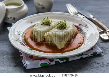 Cabbage roll, golubtsi in ceramic bowl on rustic wooden background, traditional Ukrainian cuisine.