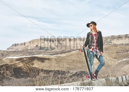 Stylish red-haired women ap and denim overalls standing on a bump at the highway in the mountains with a longboard