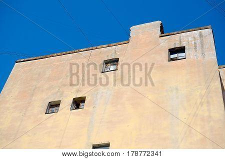 Wall gloomy house with small windows. Blue sky.