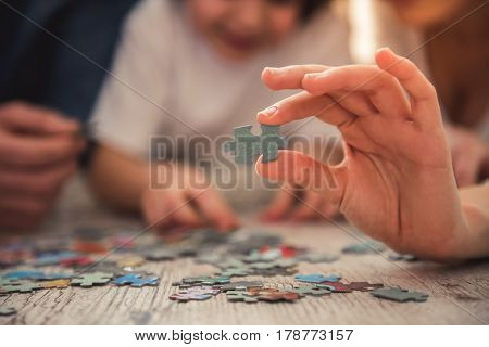 Little girl and her young parents are doing jigsaw puzzle while lying on the floor at home