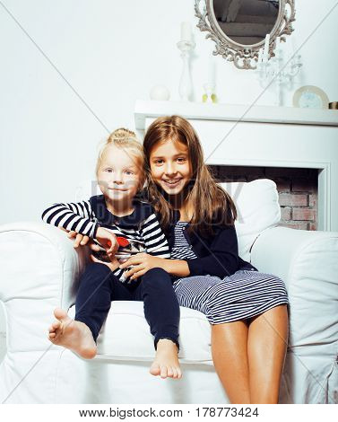 two cute sisters at home interior playing, little happy smiling girl in interior, lifestyle modern real people concept huggings close up