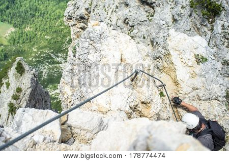 Man climbing in rock, Climber in nature, man on via ferrata, summer sports in mountains